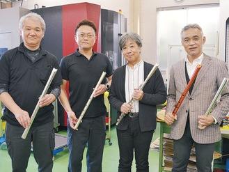 メタル尺八を手にする小村工場長、内川社長、三塚さん、宗安社長(左から)