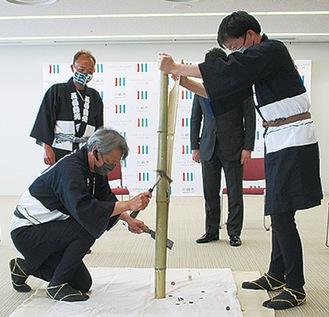 寄付金が入った竹を割る関係者
