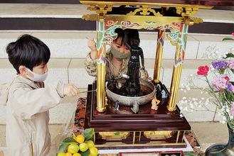 釈迦像に甘茶をかける兄弟