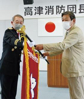 団旗を引き継ぐ武笠団長(左)と持田前団長
