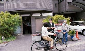 撤去作業が進む最中、近隣住民への説明に追われる井上洋治さん(右)と憲治さん(中央)