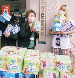 寄付に訪れた女性従業員と納米館長(中央)=同センター提供