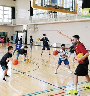 コーチの指示のもとドリブル練習に取り組む児童