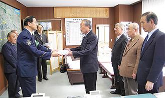 褒賞品を贈呈する菅原署長と受け取る2個人と団体代表の2人(17日、多摩警察署 署長室)
