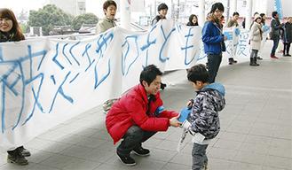 手づくりの横断幕を持って登戸駅で義援金を募る専修大学の学生