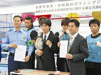 協定書を手にする菅原署長(左)と新田会長(右2番目)