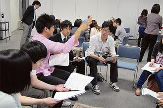 学生らが運営や進行役などのグループに分かれ、話し合った(9日、区役所)
