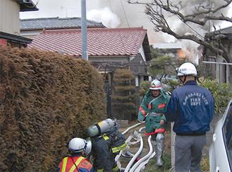 栗谷の火災現場で消火にあたる消防士や消防団員(17日)