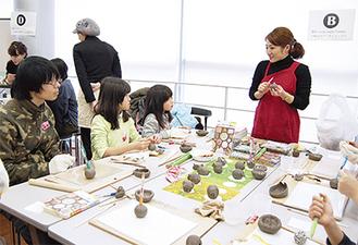 粘土でいろいろな形を作る参加者