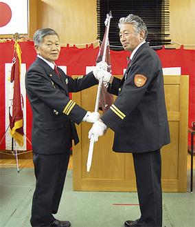 隊旗を手渡す松澤団長(左)