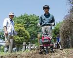 日差しが照りつける中、耕うん機を使って種まきの準備を進めるメンバー