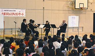 児童の間近で美しい音色を奏でる交響楽団のメンバー