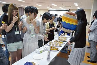 お披露目会で名産品を試食する学生や参加者ら