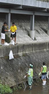 大人と子どもが連携して川からゴミを引き上げた