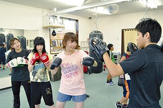 日本チャンピオンの黒田選手を相手にミット打ちに挑戦するメンバー3人(左から田中さん、淺井さん、伊藤さん)