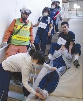 利用者が安全に避難できる方法を確かめる施設の職員