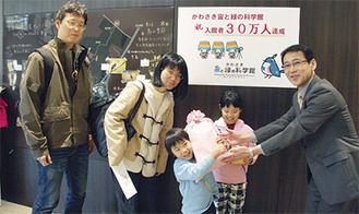 山田友之館長から記念品を受け取る堀田さん家族