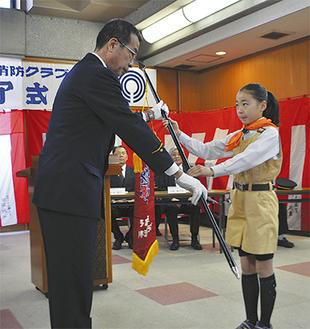 修了式でクラブ旗を返還する田村さん(右)