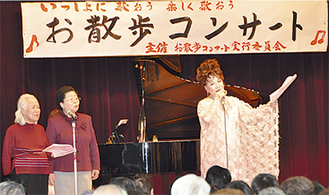 参加者と熱唱する古渡さん(右)