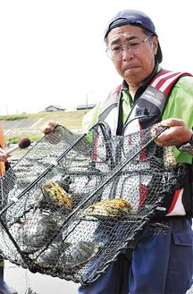 捕獲したミドリガメを前に多摩川の実態を訴える山崎さん