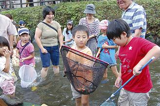 網で魚を捕まえる子どもたち