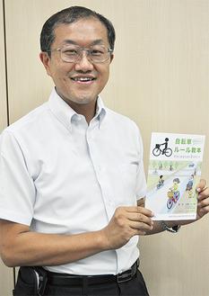 冊子を手にする野口浩史副代表