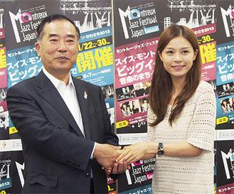 細川千尋さん(右)と握手を交わす山田長満実行委員長