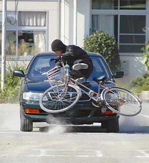 車と自転車が衝突し、大きな衝撃音が校庭に響き渡った