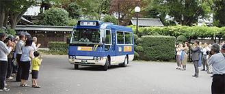 昨年7月に試行運行が行われ、出発式で地元の住民らがコミュニティバスを送り出した
