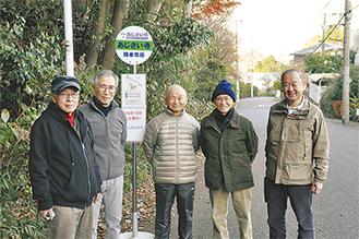 設置されたばかりのバス停を前に笑顔を見せる協議会のメンバー(8日撮影)