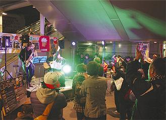 駅前で開かれたコンサートを楽しむ参加者ら