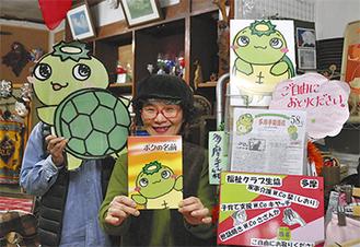 カメぱっぱで飾られた店内で、絵本を手にする笹部さんとPLUTOさん