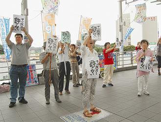 「アベ政治を許さない」とポスターを掲げ、声を上げる参加者ら(18日、登戸駅のペデストリアンデッキで)