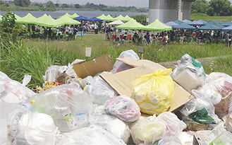 山積みになったゴミの向こうでバーベキューに興じる人で賑わう登戸の多摩川河川敷(7月12日撮影)