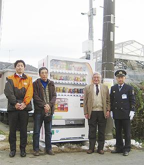 上部に防火防犯カメラが設置された自動販売機と導入に貢献した各メンバー