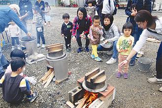 マシュマロをかまどの火であぶって食べる参加者たち