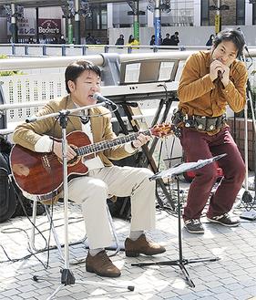 ギターを手に歌う山川さん(左)