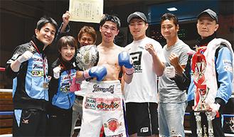 新田会長(左)らと喜びを分かち合う黒田選手(中央)=同ジム提供