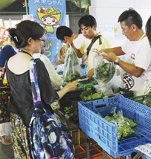 会話を交わしながら、野菜を販売する農業者ら