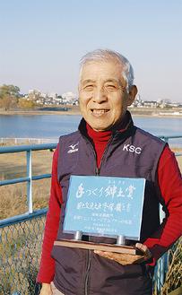 前回受賞の盾を持つ松井さん