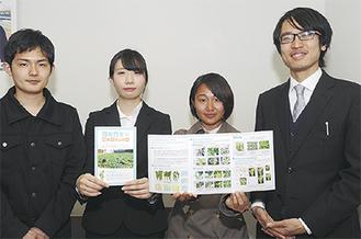 柘植さん(右)、栽培マニュアルを手にする溝田さん(右から3人目)ら明大生=28日、市庁舎