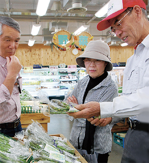 「生で食べてもおいしいですよ」と買い物客に説明する、生産者の梅沢さん(右)