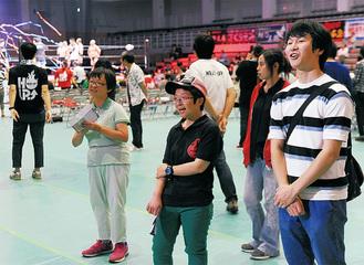 障害者スタッフと会場案内を行う、ゼミ卒業生の小山さん(右)
