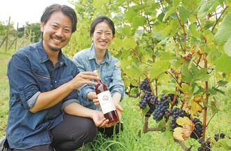 できたばかりのワインを手にする山田さんと妻・みずほさん