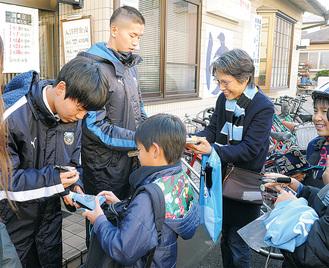 宿河原駅前商店会でサインに応じる奈良選手(右)、原田選手
