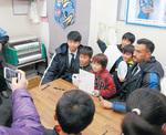 長沢商店会のサイン会で交流するジェームズ選手(右)、宮代選手