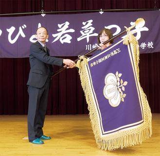 校旗を持つ西尾委員長(左)と佐藤校長=同校提供