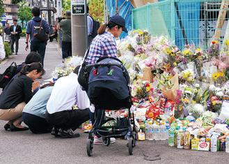 花や飲み物を供え、手を合わせる人が絶えず訪れている現場付近=先月29日