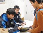 長沢商店会でサインに応じる原田選手(左)と安藤選手