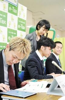 タブレットを操作して申告する古橋岳也選手(左)
